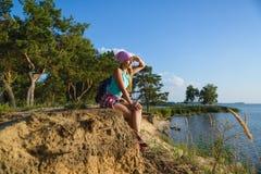 Nastoletni dziewczyny obsiadanie na piasek falezie patrzeje morze Podróży i turystyki pojęcie Obraz Stock