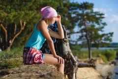 Nastoletni dziewczyny obsiadanie na piasek falezie patrzeje morze Podróży i turystyki pojęcie Zdjęcia Stock