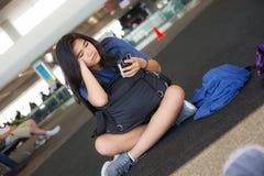 Nastoletni dziewczyny obsiadanie na podłoga przy lotniskowym patrzeje smartphone fotografia royalty free
