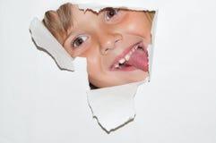 Nastoletni dziewczyny spojrzenie od dziury w białym papierze Zdjęcia Royalty Free