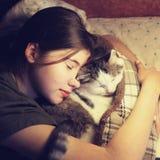 Nastoletni dziewczyny uściśnięcia cuddle kot w łóżku zdjęcie royalty free