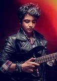 Nastoletni facet bawić się na gitarze Obrazy Royalty Free
