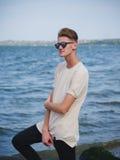 Nastoletni facet relaksuje blisko rzeki Przypadkowa chłopiec outdoors na zamazanym tle Nowożytny mody pojęcie kosmos kopii obrazy royalty free