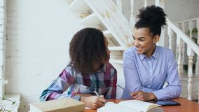 Nastoletni kędzierzawy z włosami mieszany biegowy młodej dziewczyny obsiadanie przy stołu koncentrować skupiam się uczący się lek obraz royalty free