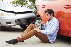 Nastoletni kierowca Robi rozmowie telefonicza Po wypadku ulicznego obrazy stock