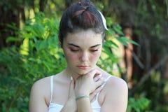 Nastoletni patrzejący w dół rękę przy klatką piersiową Fotografia Stock