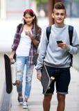 Nastoletni przyjaciół nieść jeździć na deskorolce w mieście Zdjęcia Stock