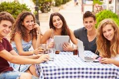 Nastoletni przyjaciele Siedzi Przy Cafï ¿ ½ Używać Cyfrowych przyrząda obrazy royalty free