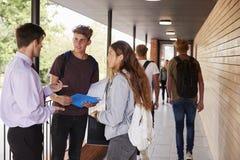 Nastoletni ucznie Opowiada nauczyciel Na zewnątrz budynków szkoły fotografia royalty free