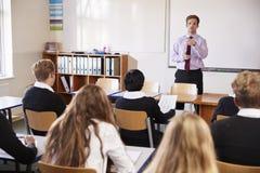 Nastoletni ucznie Słucha Męski nauczyciel W sala lekcyjnej obrazy stock