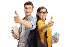 Nastoletni ucznie z plecakami i książkami robi kciukowi w górę gestur fotografia royalty free