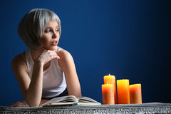Nastoletni w srebnej peruce i białym singlet pozuje z książką z bliska niebieska tła Fotografia Stock