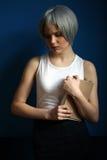 Nastoletni w srebnej peruce pozuje z książką z bliska niebieska tła Zdjęcie Royalty Free