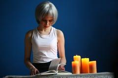 Nastoletni wzorcowy pozować z książką i świeczkami z bliska niebieska tła Obraz Royalty Free