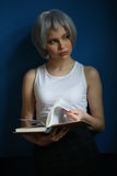 Nastoletni z srebnym włosy leafing przez książki z bliska niebieska tła Obraz Royalty Free