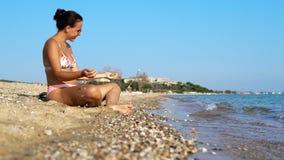 nastoletni z szkłami relaksuje na plaży wybrzeża miotania kamieniach zdjęcie royalty free