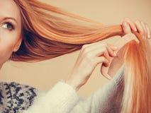 Nastoletnia blondynki dziewczyna szczotkuje jej włosy z gręplą Obraz Royalty Free