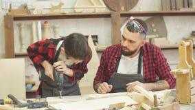 Nastoletnia chłopiec pomaga jego ojca świder dziury w drewnianej desce zdjęcie wideo