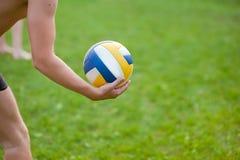 Nastoletnia chłopiec bawić się plażową siatkówkę Siatkówka gracz na trawie bawić się z piłką, siatkówki piłka w jego ręce zdjęcia stock