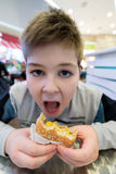 Nastoletnia chłopiec je hamburgeru n kawiarni Zdjęcie Royalty Free