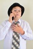 Nastoletnia chłopiec opowiada na telefonie komórkowym przy lekkim tłem Obraz Stock