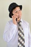 Nastoletnia chłopiec opowiada na telefonie komórkowym przy lekkim tłem Zdjęcia Stock