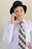 Nastoletnia chłopiec opowiada na telefonie komórkowym przy lekkim tłem Obrazy Stock