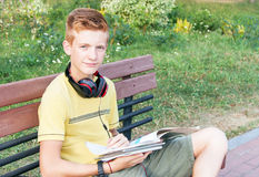 Nastoletnia chłopiec siedzi z książkami na ławce obraz royalty free