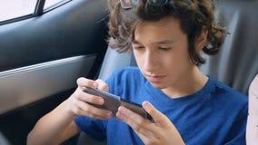 Nastoletnia chłopiec używa telefon w samochodzie podczas gdy podróżujący zdjęcie wideo