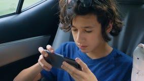 Nastoletnia chłopiec używa telefon w samochodzie podczas gdy podróżujący obrazy stock