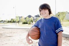 Nastoletnia chłopiec z koszykówką Zdjęcia Royalty Free