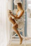 Nastoletnia dziewczyna bawić się z misiem podczas gdy siedzący na krześle blisko okno Fotografia Royalty Free