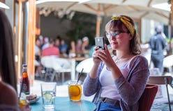 Nastoletnia dziewczyna bierze fotografię na telefonie komórkowym w kawiarni zdjęcia royalty free