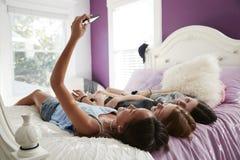 Nastoletnia dziewczyna bierze selfie z dwa przyjaciółmi kłama na łóżku zdjęcie royalty free