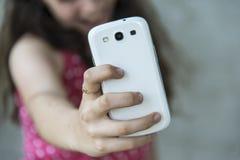 Nastoletnia dziewczyna bierze selfie z jej telefonem obraz royalty free