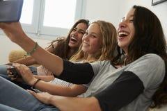 Nastoletnia dziewczyna bierze selfie z przyjaciółmi używa jej smartphone obrazy stock