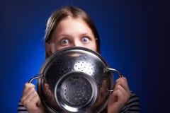 Nastoletnia dziewczyna chuje jej twarz za colander obraz stock