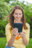 Nastoletnia dziewczyna czyta elektroniczną książkę Zdjęcia Stock