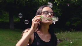 Nastoletnia dziewczyna dmucha mydlanych bąble w lecie zdjęcie wideo