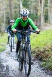 Nastoletnia dziewczyna i chłopiec jechać na rowerze na lasowych śladach fotografia stock