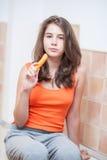 Nastoletnia dziewczyna je marchewki w pomarańczowej koszulce Zdjęcie Stock