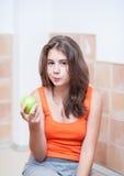 Nastoletnia dziewczyna je zielonego jabłka w pomarańczowej koszulce Obraz Royalty Free