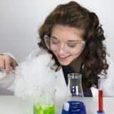 Nastoletnia dziewczyna jest ubranym gogle robi nauka eksperymentowi Obrazy Royalty Free