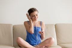 Nastoletnia dziewczyna jest ubranym hełmofony cieszy się muzykę na telefonie komórkowym appl Obrazy Royalty Free