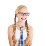 Nastoletnia dziewczyna jest ubranym mundurek szkolny i szkła. Uśmiechnięta twarz, brasy na twój zębach. Fotografia Royalty Free