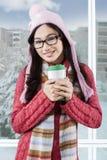 Nastoletnia dziewczyna jest ubranym pulower i chwyty filiżanka Fotografia Stock