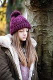 Nastoletnia dziewczyna jest ubranym woolen kapeluszową pozycję obok drzewa Fotografia Stock