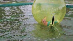 Nastoletnia dziewczyna ma zabawy kręcenie wśrodku zorb na wodzie i bieg zdjęcie wideo
