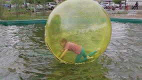 Nastoletnia dziewczyna ma zabawy kręcenie wśrodku zorb na wodzie i bieg zbiory wideo
