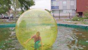 Nastoletnia dziewczyna ma zabawy kręcenie wśrodku zorb na wodzie i bieg zbiory